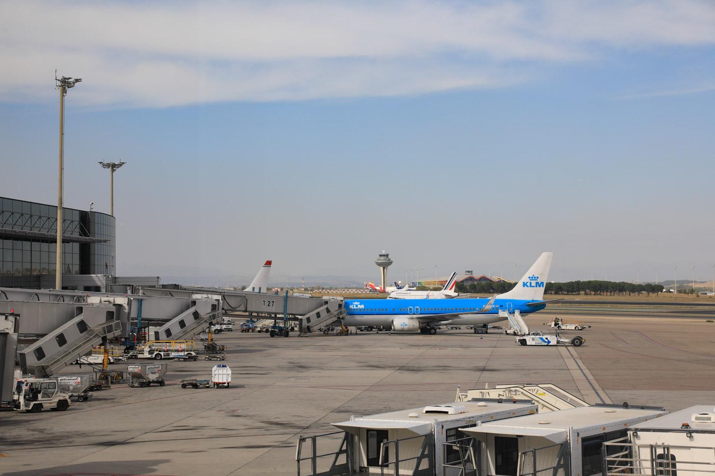 Een KLM vliegtuig staat aan de gate op de luchthaven van Madrid.